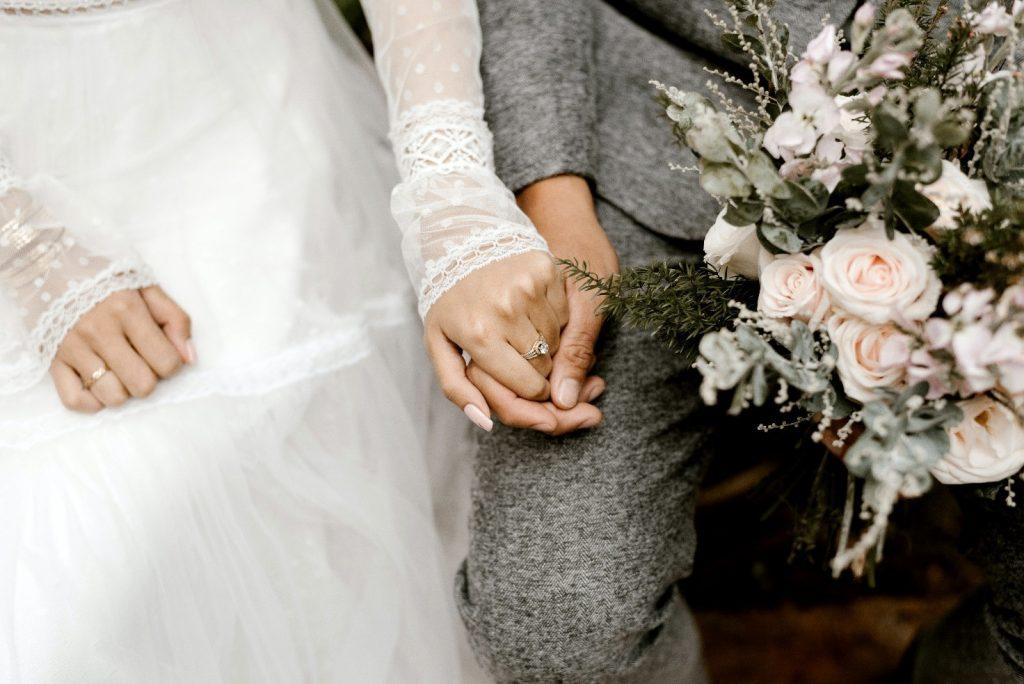 Noivos de mãos dadas ouvem emocionados o roteiro para celebrante de casamento (Imagens: Pexels)